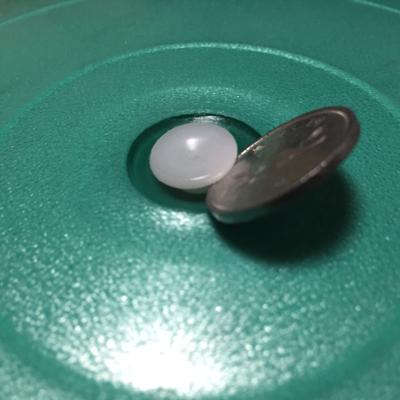 1円玉をバランスボールの栓に挟む