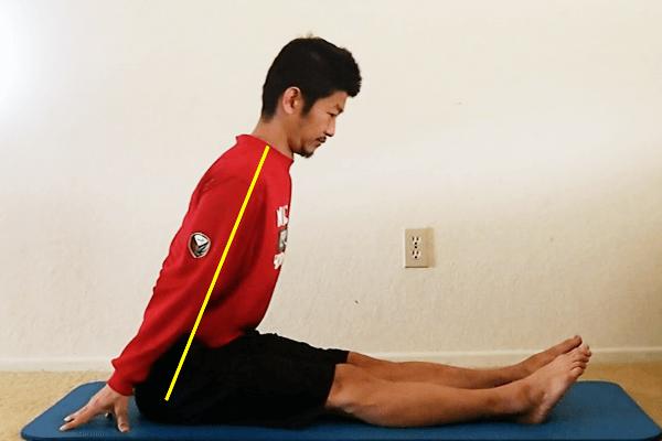 バリスティックストレッチ:長座前屈から前傾姿勢になり、ハムストリングやふくらはぎの裏をストレッチする