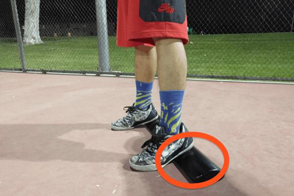 踵の下に重りのプレート等を滑り込ませ、強制的に踵を上げた状態を作り出して重心をつま先へとシフトさせる
